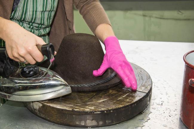 Das Ranfteln - eine der Bearbeitungs-Moeglichkeiten eines Hutes. Hier wird mit dem Buegeleisen, Wasser und der Ranftelschnur die Krempe geformt.
