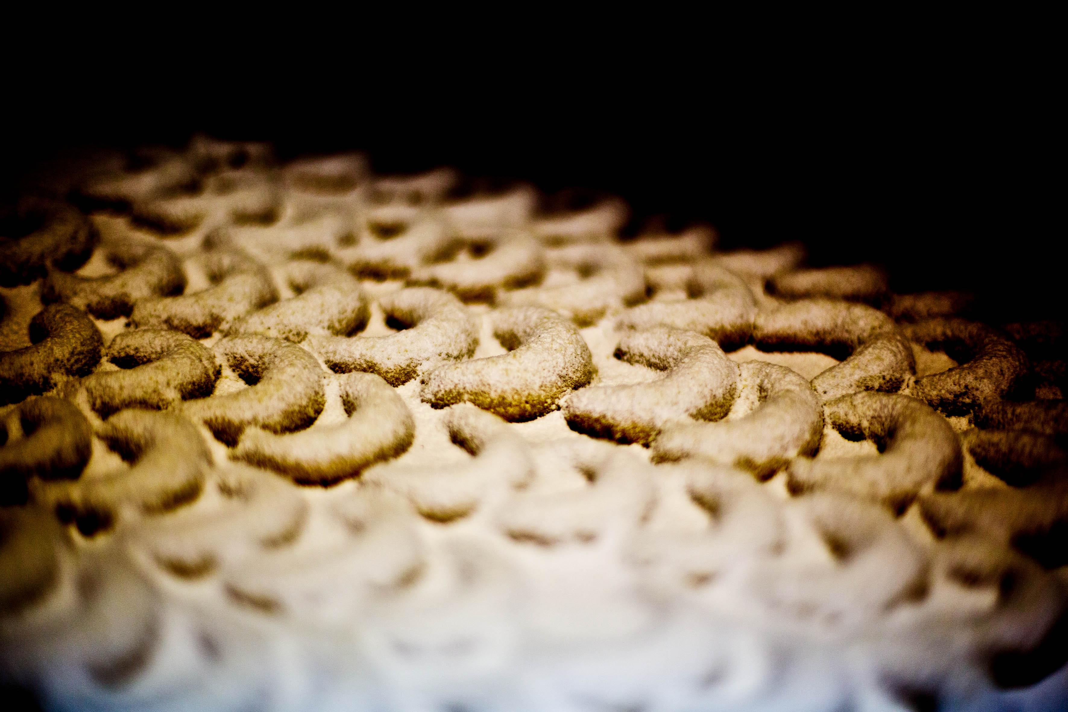 fertige Vanillekipferl dick mit Vanillezucker bestreuen