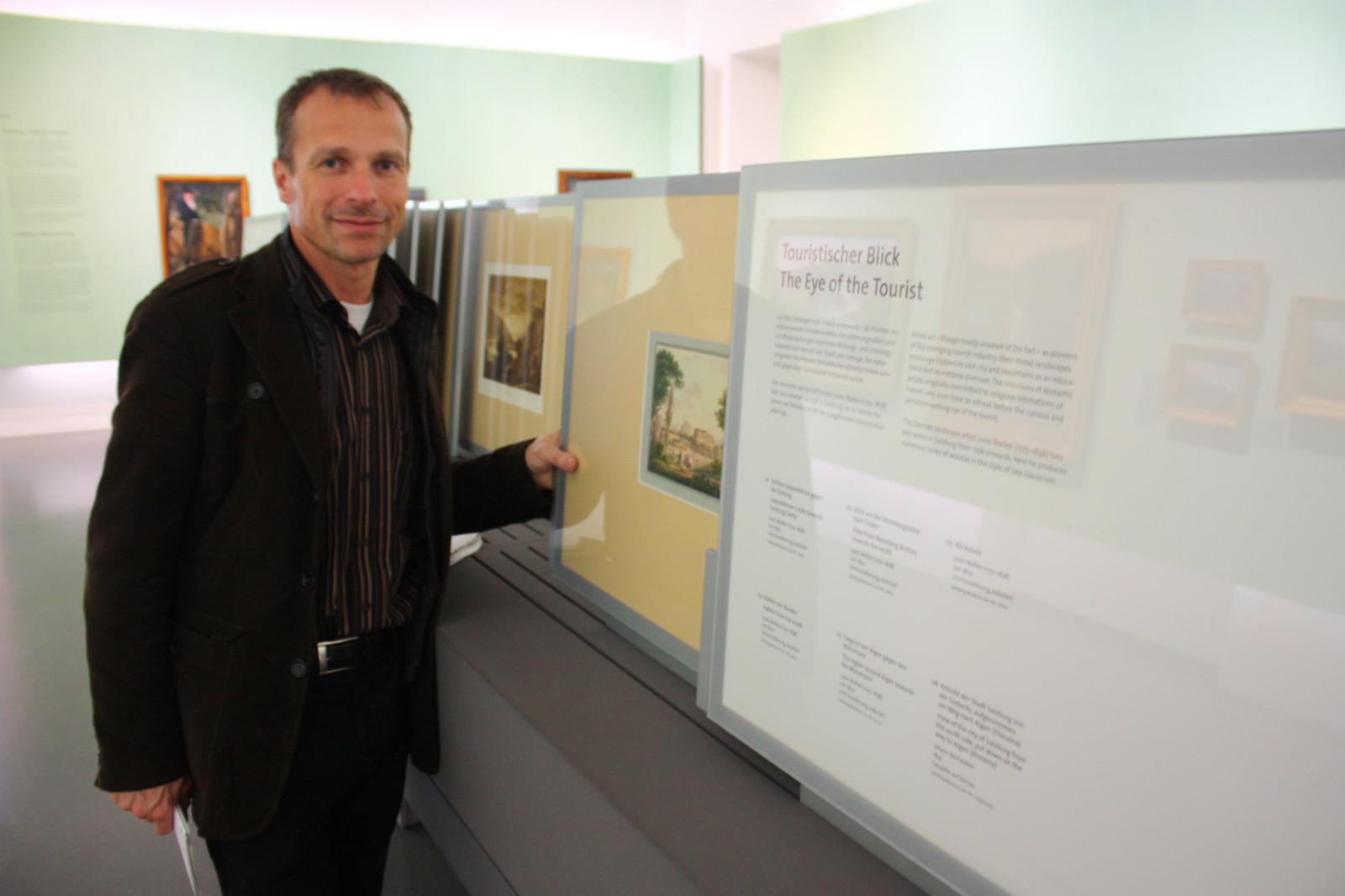 Museumsleiter Husty führt die informativen Schiebewände vor