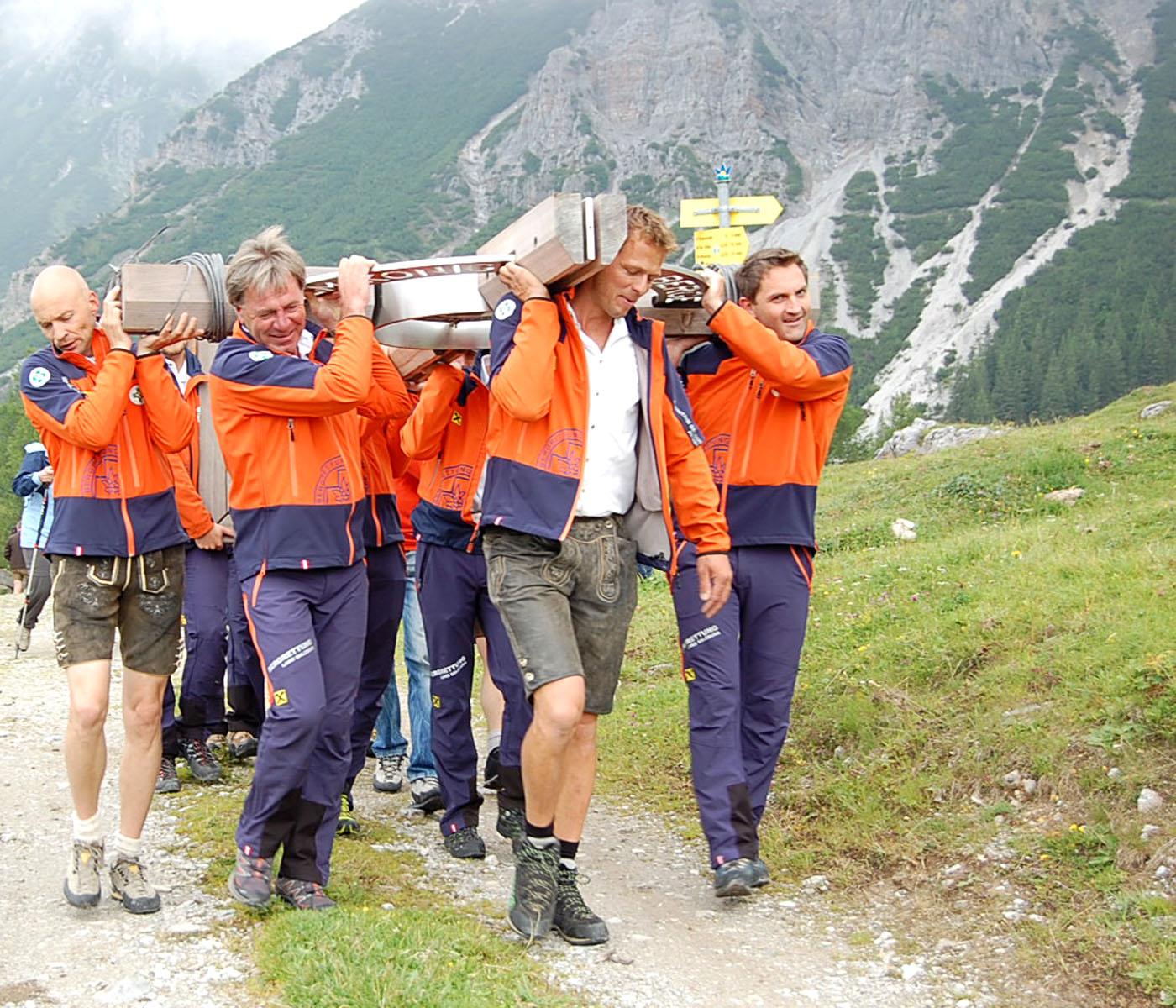 Dientener Bergretter trugen das neue Gipfelkreuz zur Weihe bei der Erichhütte.