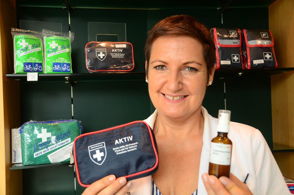 Apothekerin Karin Planitzer mit einem Erste-Hilfe-Paket und Insektenspray
