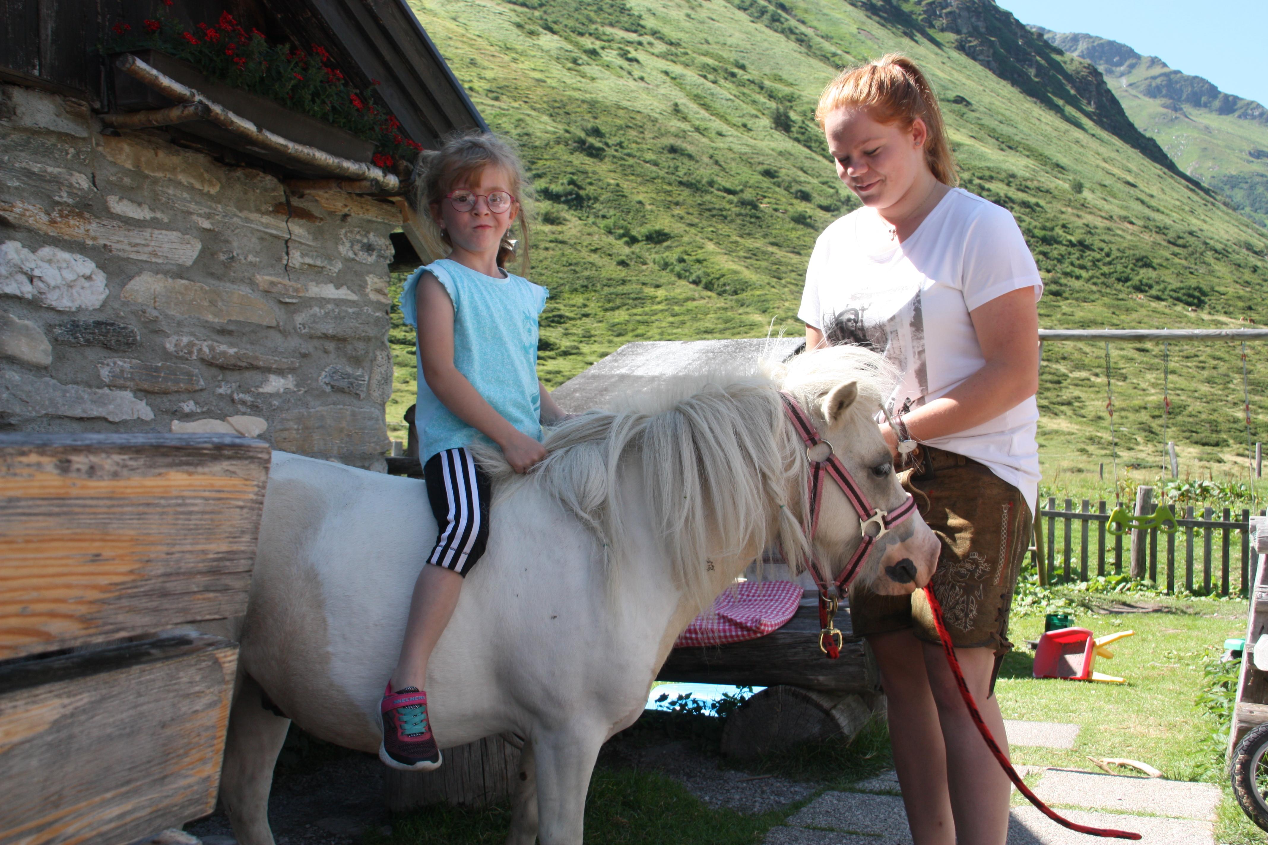 © SalzburgerLand Tourismus, Martina Egger, Eva-Maria und Pony Charly haben viel Spaß und drehen eine Runde um die Hütte
