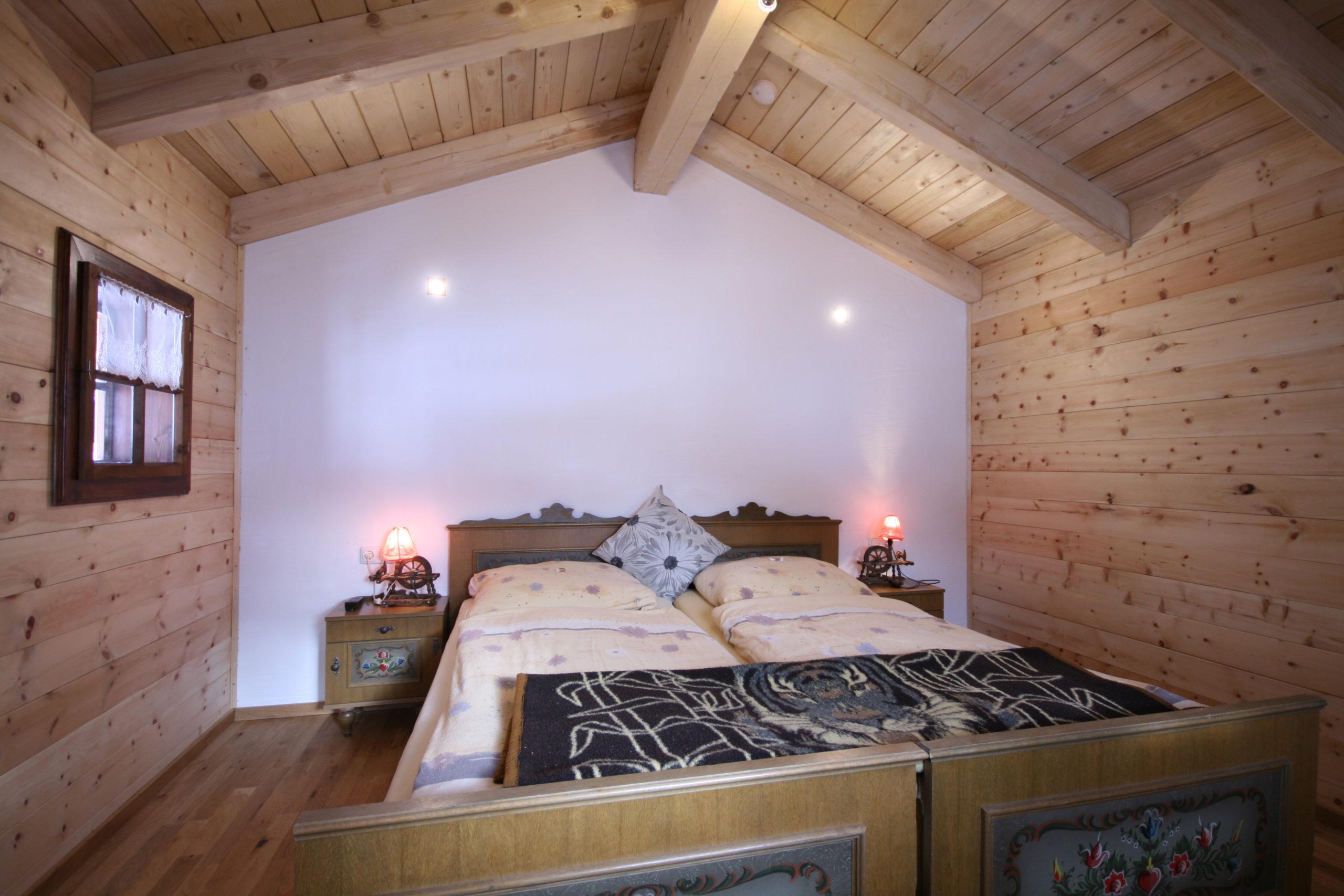 ©  Almliesl / Schlafzimmer mit Doppelbett im Dachgeschoß mit Zirbenverkleidung