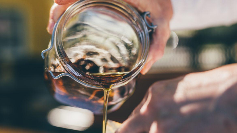 Jemand lässt Honig aus einem Glas tropfen