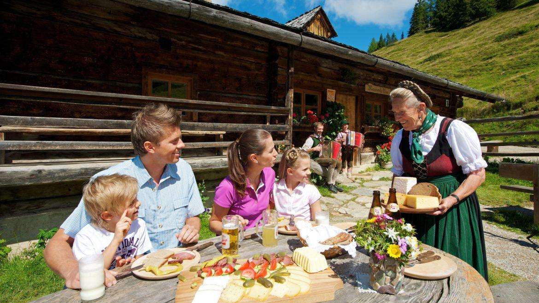 Hüttenwirtin serviert Familie frische Almprodukte.