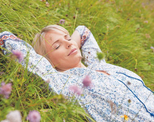 Junge Frau schläft auf der blühenden Almwiese