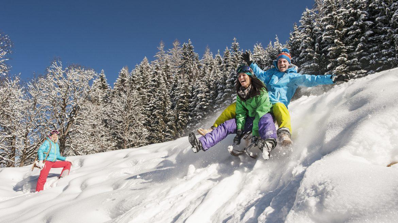 Junges Paar rodelt einen verschneiten Hügel hinab.