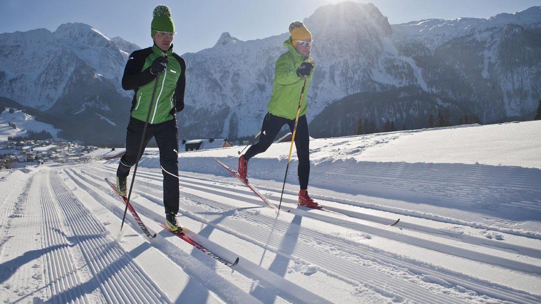 Paar auf Langlaufskiern in der gespurten Loipe bei Sonnenschein