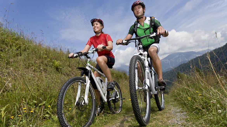 Junges Paar fährt auf weißen Mountainbikes auf Schotterweg über eine Wiese