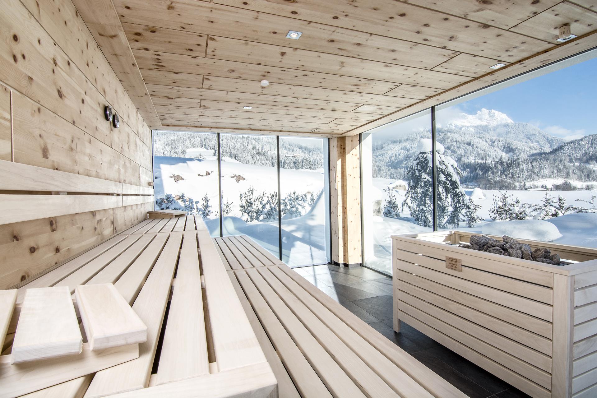 Leere Zirbensauna mit Blick aus dem Panoramafenster auf die verschneite Landschaft