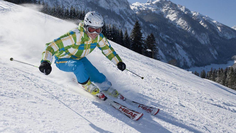 Skifahrer mit blauer Skihose, grün-karierter Jacke und weißem Helm auf der Piste