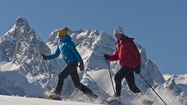 Paar beim Schneeschuhwandern vor winterlicher Bergkulisse