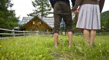 Pärchen spaziert barfuß über die Wiese und hält sich dabei an den Händen (Rückansicht)