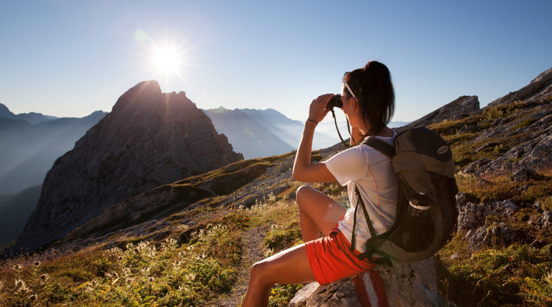 Wanderin sitzt auf einem Stein und beobachtet den Sonnenuntergang über den Bergen durch ein Fernglas.