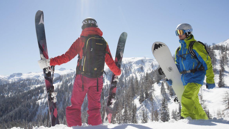 Snowboarder mit Rucksack und Snowboard in der Hand blickt Richtung Tal im verschneiten Altenmarkt-Zauchensee