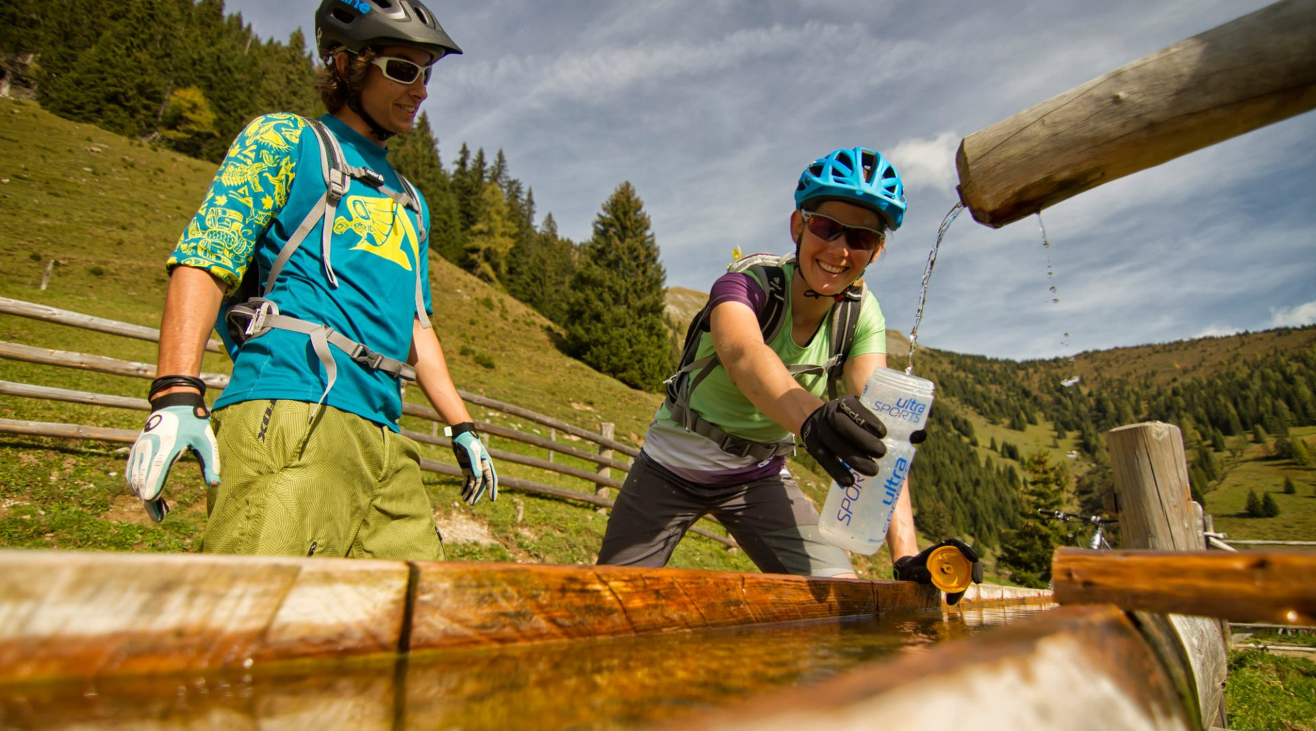 Ein Mountainbiker und eine Mountainbikerin mit Helm und Sonnenbrille stehen am Brunnen und füllen eine Wasserflasche mit Wasser auf