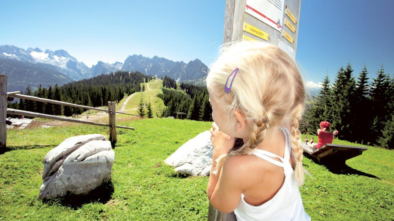Ein Mädchen mit blonden Zöpfen auf der Alm