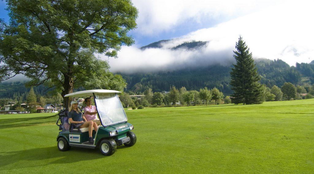 Mann und Frau sitzen im Golfbuggy am Golfplatz