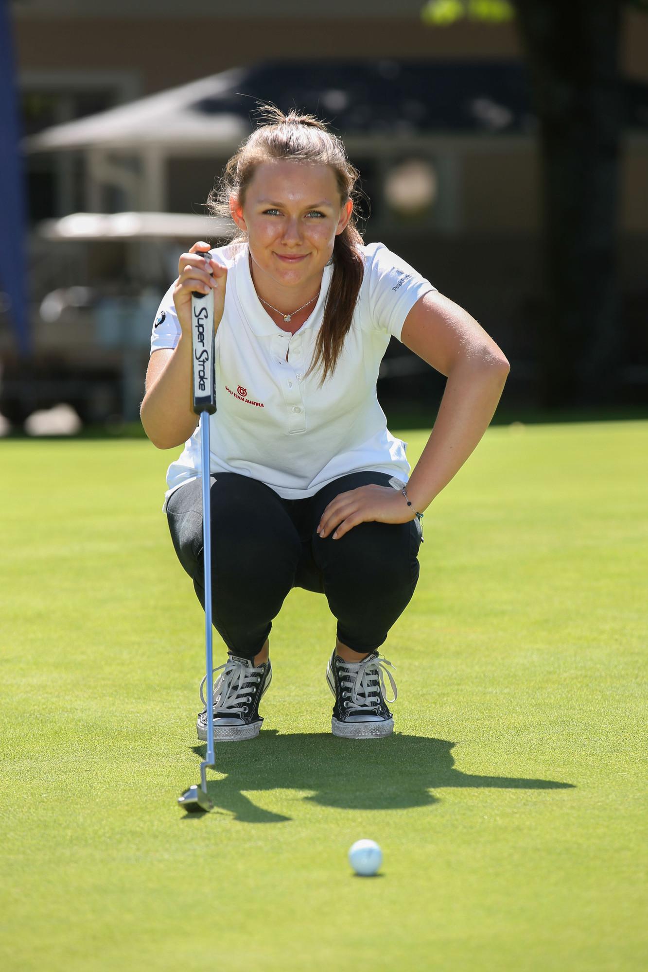 Junge Golferin hockt am Putting Green und denkt über ihren Putt nach