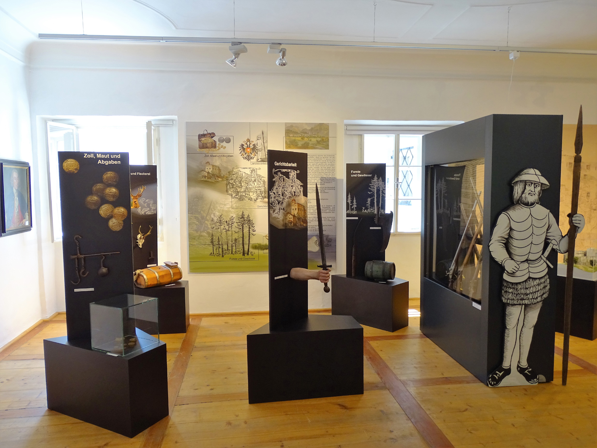 Innenraum des Museums auf der Burg Golling - dunkle Säulen präsentieren die Exponate