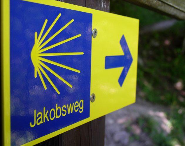 Blau-gelber Wegweiser des Jakobsweges mit der stilisierten Jakobsmuschel als Logo