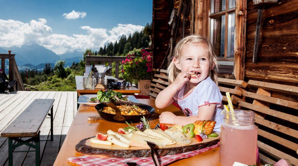 Blondes Mädchen genießt vor der Hütte sitzend die Almjause