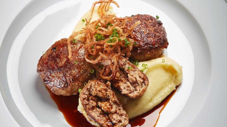 Frische Fleischlaibchen mit Karoffelpüree, gerösteten Zwiebeln und Bratensaft