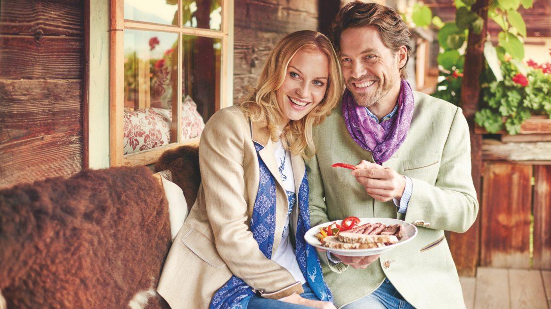 Verliebtes Paar mit Trachtengewand genießt Jause auf der Hausbank vor der Hütte und lacht