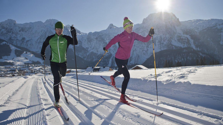 Mann und Frau in Winter-Sportbekleidung auf der Loipe