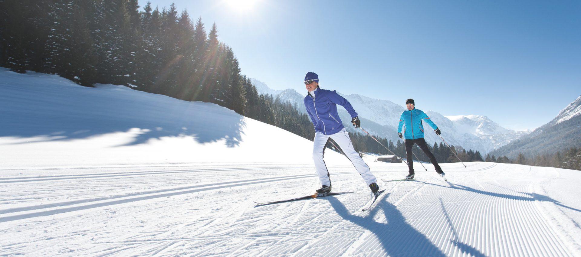 Zwei Längläufer beim Skating auf der Piste im Sonnenschein.