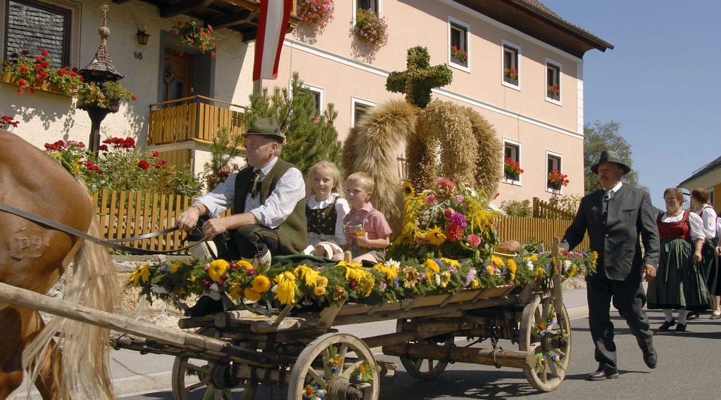 Erntkrone wird auf einem geschmückten Traktor durch den Ort gezogen