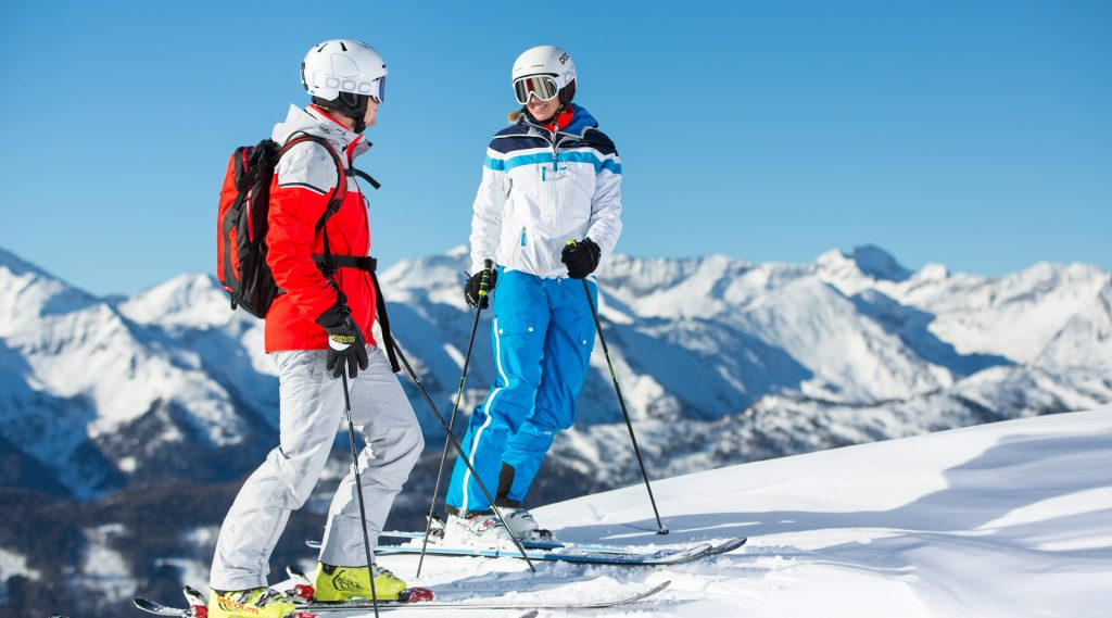 Zwei Personen in Skikleidung, mit Helm vor der Abfahrt