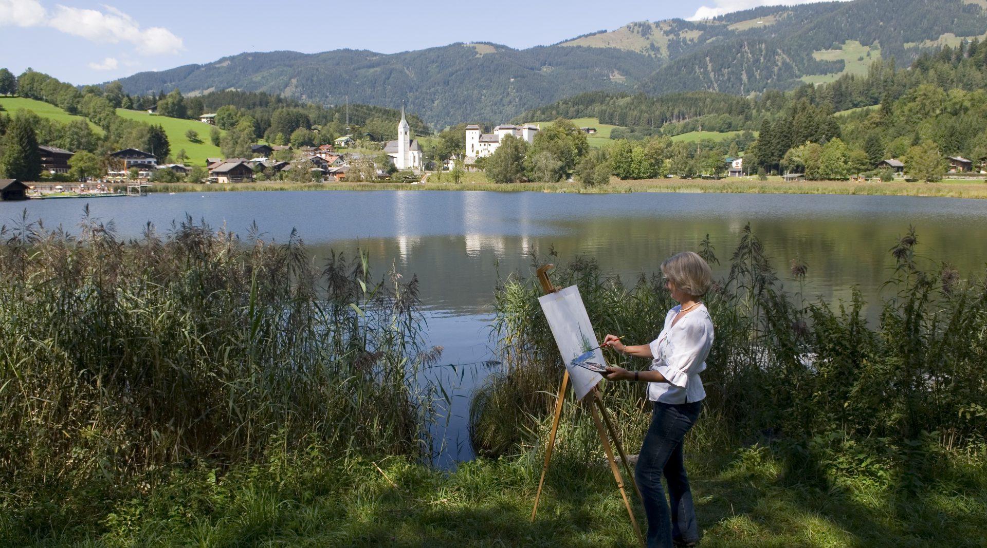 Eine Frau steht am Moorsee und malt