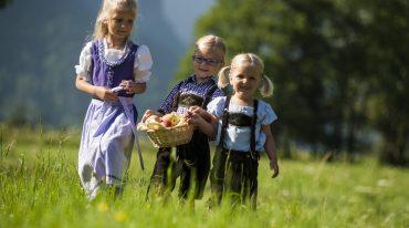 Drei Kinder spazieren über eine Wiese