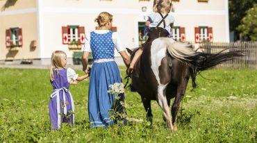 Ein Kind reitet auf einem Pony, die Mutter und das andere Kinder gehen händchenhaltend nebenbei her (Rückansicht)