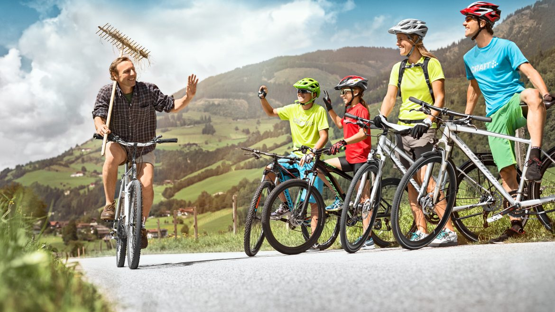 Radfahrer grüßen einen Einheimischen am Tauernradweg.