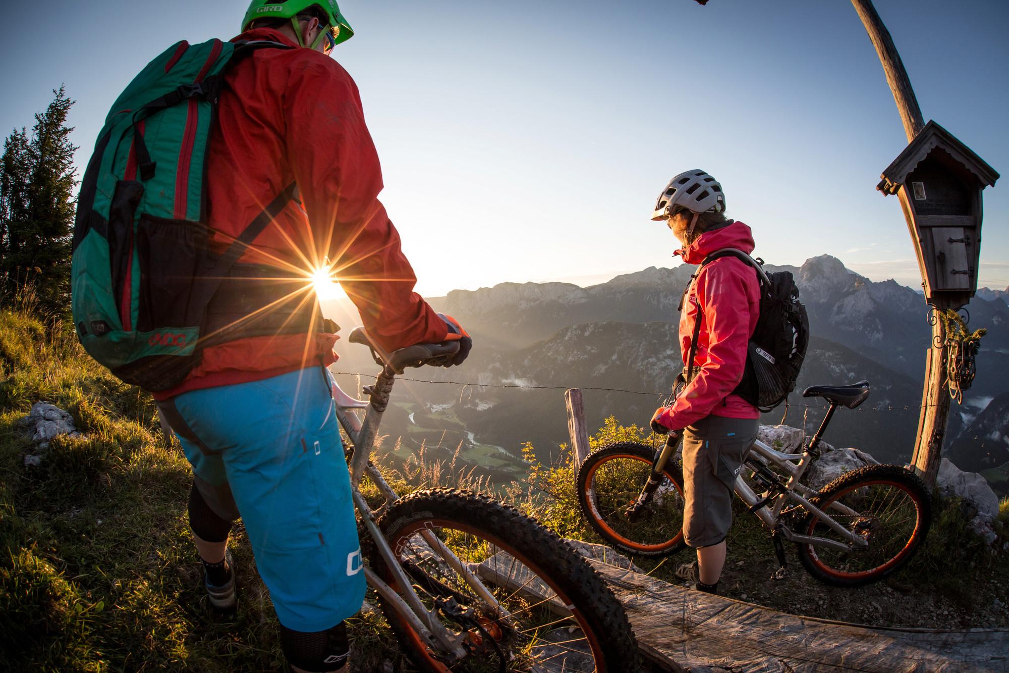 Zwei Mountainbiker stehen am Gipfel und genießen die untergehende Sonne