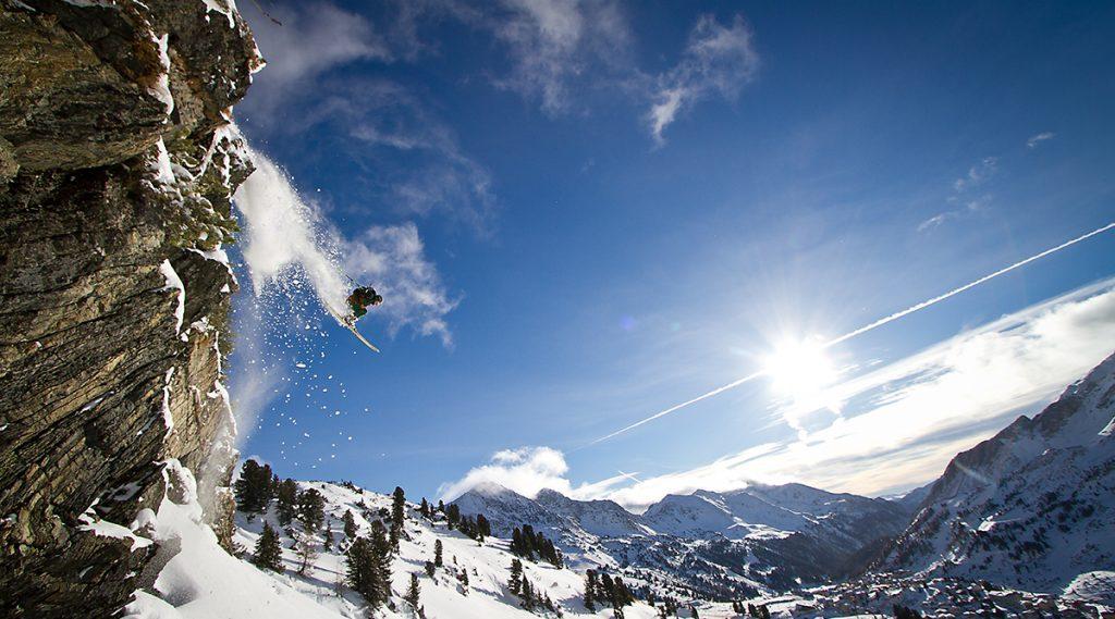 Freerider springt über Abhang in Obertauern, die Sonne scheint