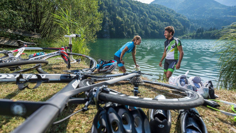 Zwei Radfahrer machen Pause am Ufer eines Sees.