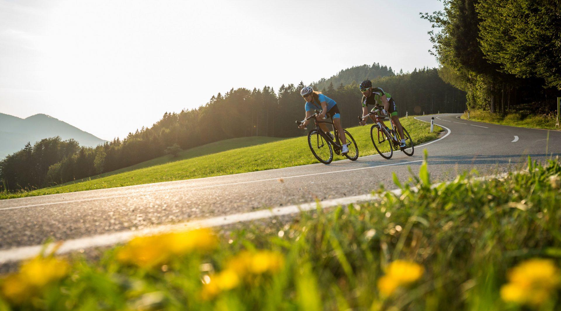 Zwei Radfahrer fahren im Sonnenuntergang bergab um die Wette
