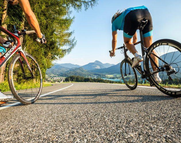 Zwei Radfahrer liefern sich auf einer einsamen Straße ein Renen entlang eines Sees.