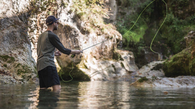 Fliegenfischer steht im Fluss und wirft seine Angelschnur aus.
