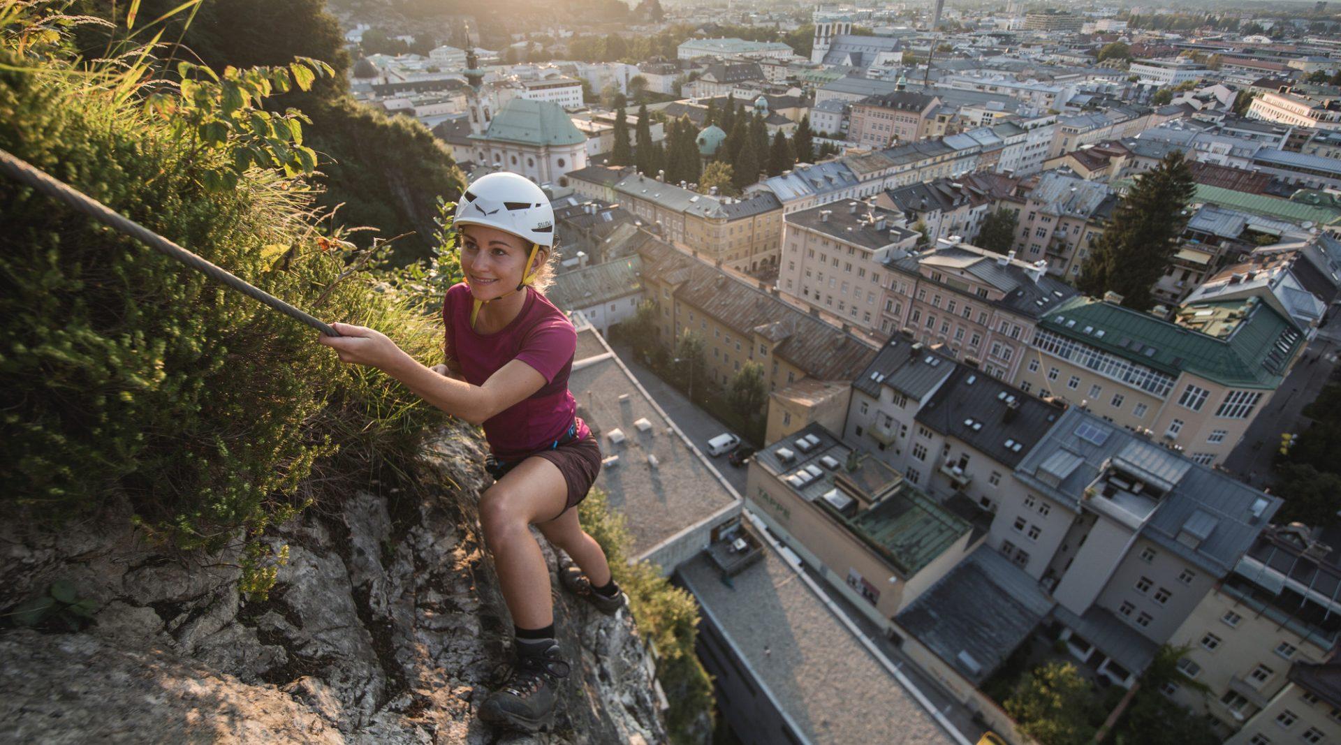 Frau klettert im Sonnenuntergang hoch über den Dächern der Stadt Salzburg am Klettersteig 'City Wall'.