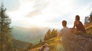 Familie genießt Sonnenuntergang auf der Alm