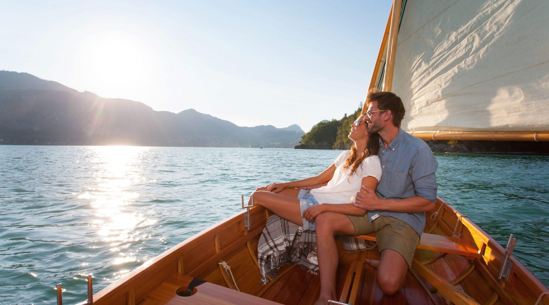 Paar genießt die Sonne beim Segeln vom Boot aus.