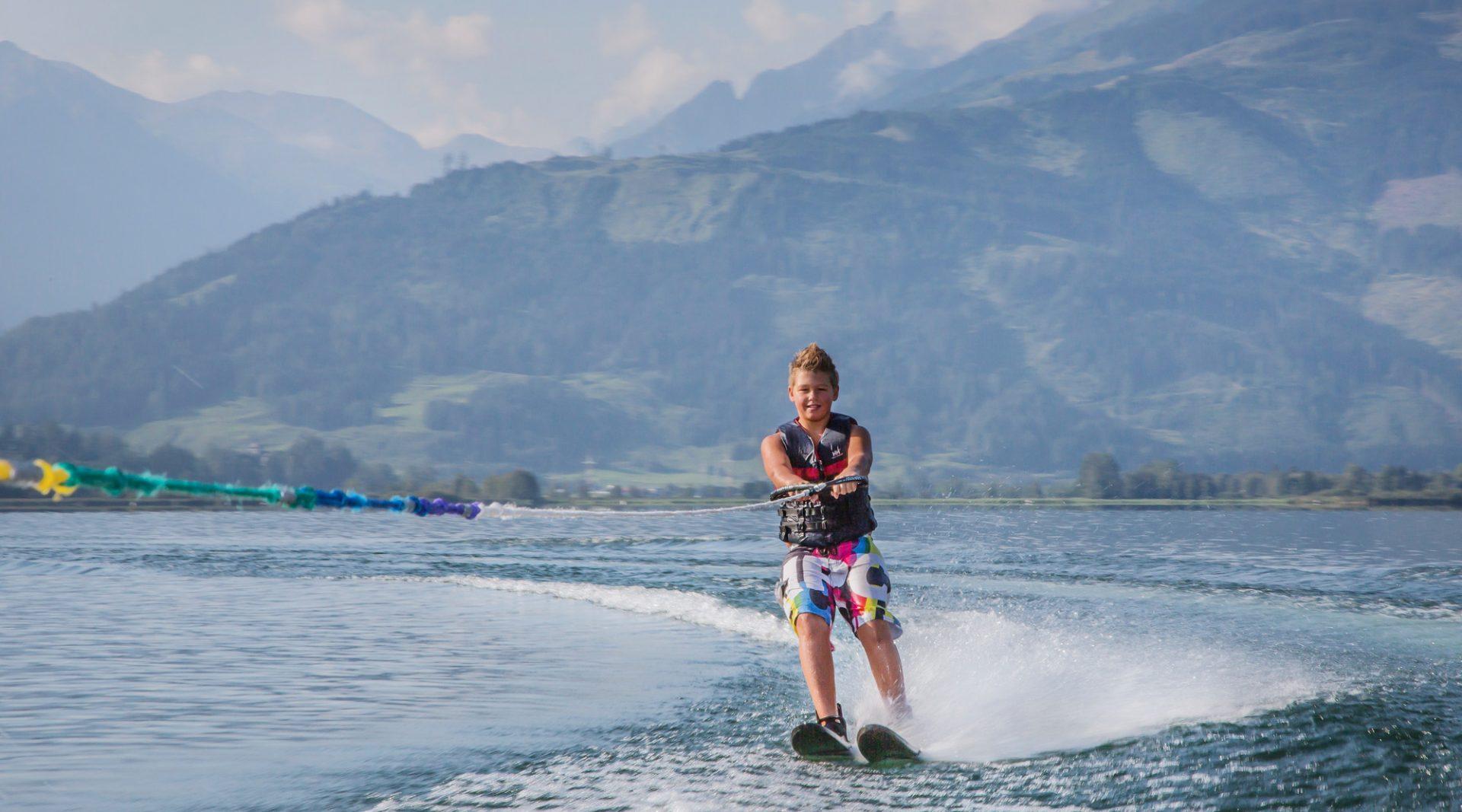 Junge fährt auf Wasserski an einem schönen Tag über einen See im SalzburgerLand.