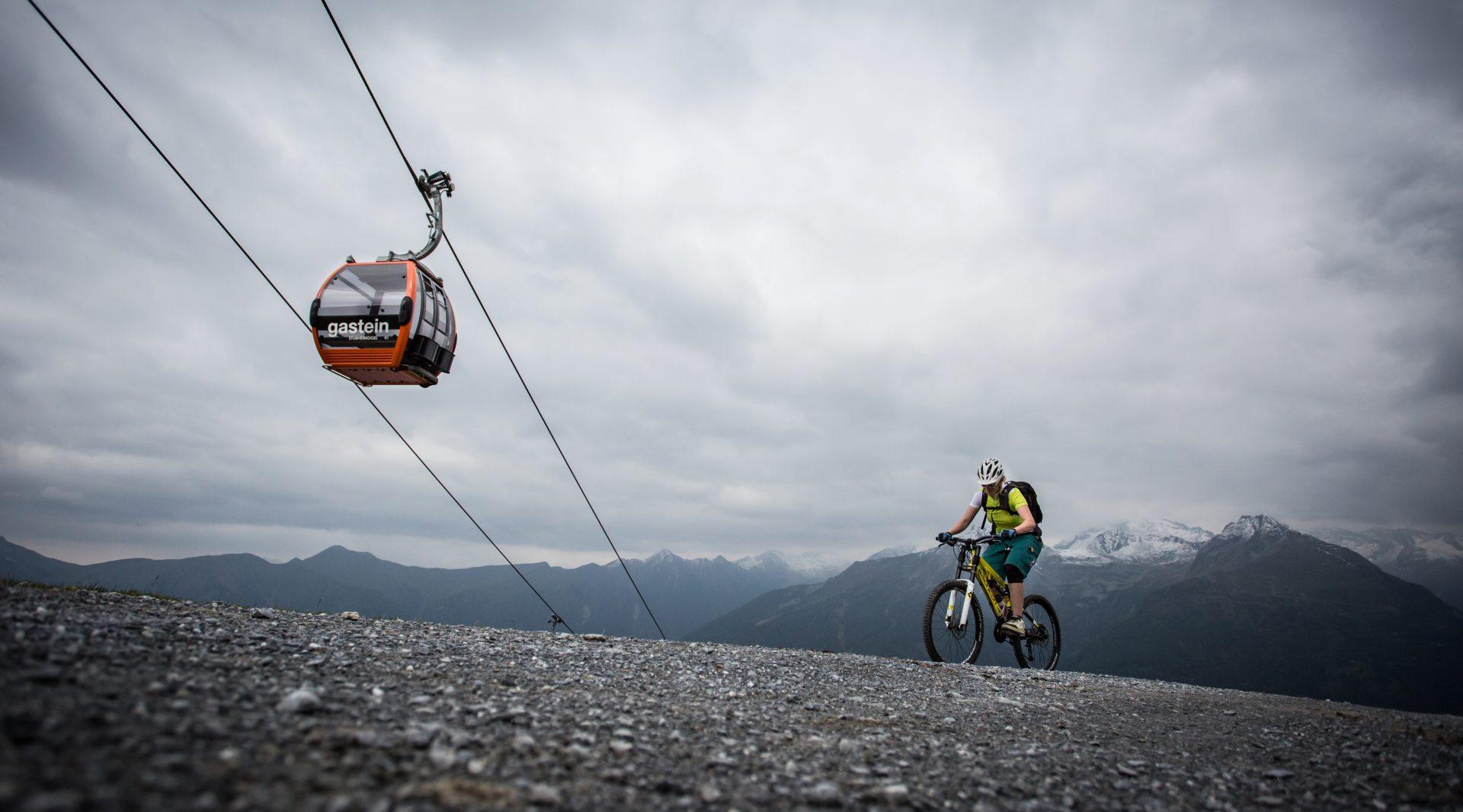 Mountainbike fährt den Berg hinauf, während eine rote Gondel über seinem Kopf hinwegfährt.