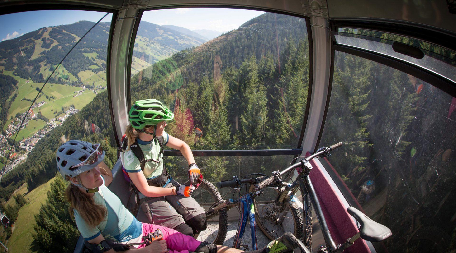 Zwei Mountainbiker sitzen neben ihren Bikes in der Gondel und genießen die Aussicht auf grüne Berghänge.
