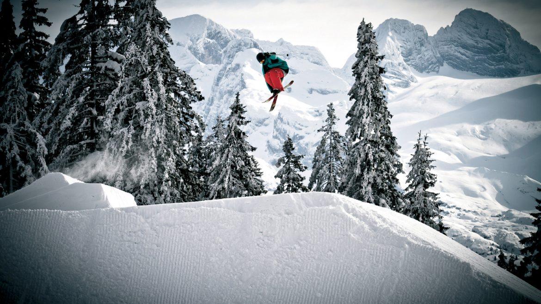 Freestyler auf Skiern hoch in der Luft in tief verschneiter Landschaft