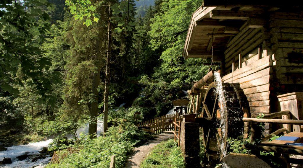 Holzmühle mit Mühlrad im Sonnenschein